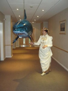 A lady takes her remote-controlled flying inflatable shark for a stroll