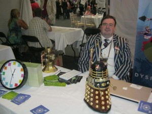 Eastercon stall with steampunk Dalek, steampunk megaphone and elements clock